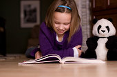 Elementary age girl reading a story on the floor with her stuffed animal.