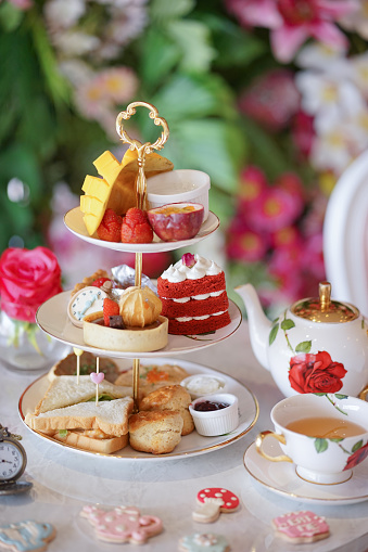 Afternoon tea. A traditional British afternoon tea party in Wonderland concept with selective focus on the red velvet heart cake. Sugar glazed cookies in fairy tales concept are scattered on the table.