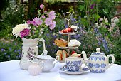 Photograph of a table set for afternoon tea. The table is covered with a white table cloth and there is a three-tiered cake stand containing a sandwich, a scone, a meringue, a cake and some strawberries and cream. There is a blue and white teapot and cup and saucer and a white china milk jug and sugar bowl. To the left there is a jug containing an arrangement of flowers. The table is standing in an English country garden. Flowers can be seen in the background.