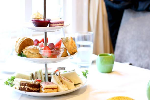 afternoon tea tre tier stativ av desserter, färsk frukt, bakverk och smörgåsar - eftermiddagste bildbanksfoton och bilder