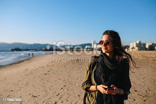 young woman walking on the Santa Monica beach. She is wearing casual clothing, an olive colored jacket, watching the sunset above the ocean.