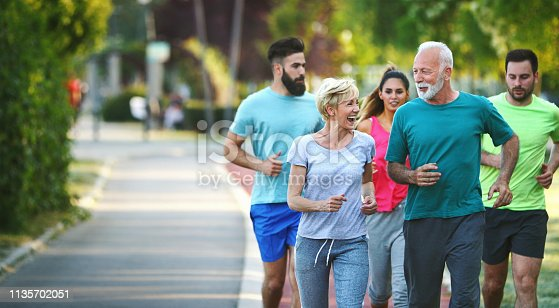 Closeup front view of group of mixed age people having a light jogging at a local park on a sunny summer afternoon. There are two seniors and three mid 20's people.