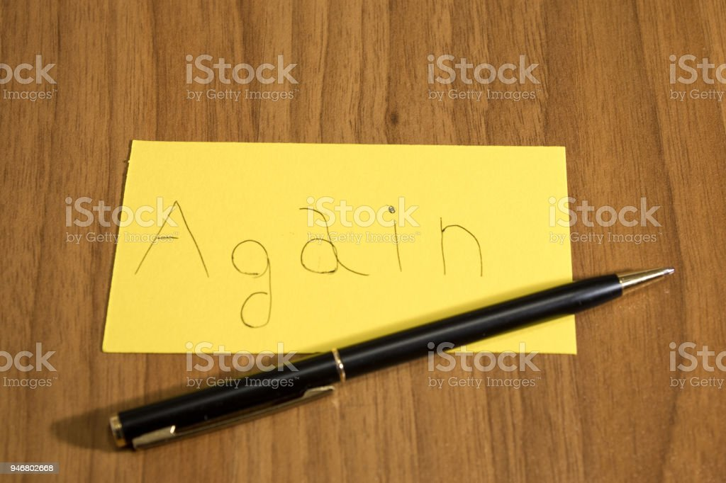 Again handwrite on a yellow paper with a pen on a table composition stock photo