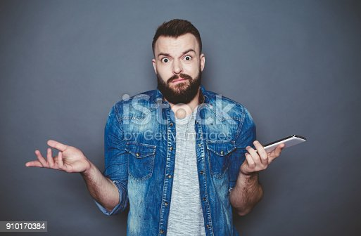 825083556istockphoto Again the same thing. A young bearded man in a denim shirt writes a message in the phone on a gray background. 910170384