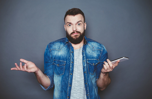 825083556 istock photo Again the same thing. A young bearded man in a denim shirt writes a message in the phone on a gray background. 910170384