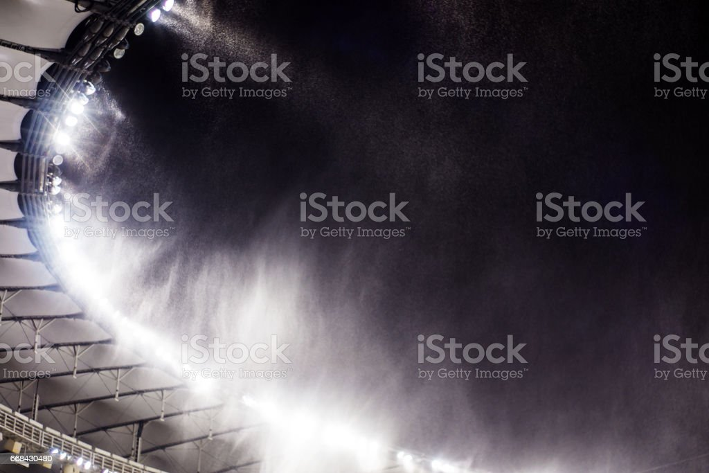 against the background of a sports stadium floodlights, flying snow stock photo