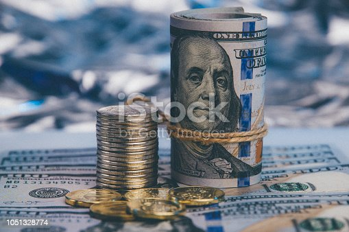 istock Against the blue backdrop of a hundred dollar bills spread out, a bundle of dollars and a stack of shiny coins. 1051328774
