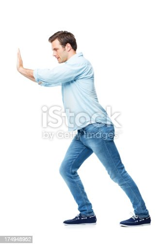 A casual young man pushing against something while isolated on a white background