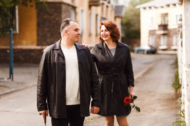 age couple in leather coats walking through the city streets in the summer. Happy man and woman forty five years old stock photo