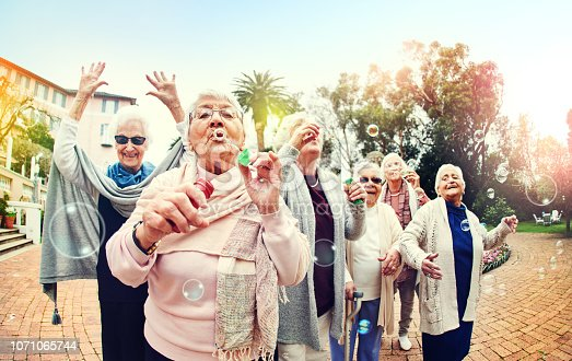 Shot of a group of senior women blowing bubbles together outdoors