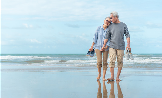 Age, Travel, Tourism and people concept - happy senior couple holding hands and walking on summer beach