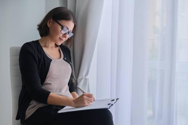 Yaş kadın sosyal hizmet görevlisi, psikolog kırpma tahtası ile pencerenin yanında oturan stok fotoğrafı
