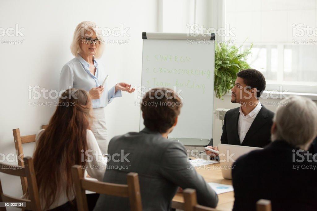 De edad a atractiva empresaria dando presentación en reunión de equipo corporativo foto de stock libre de derechos