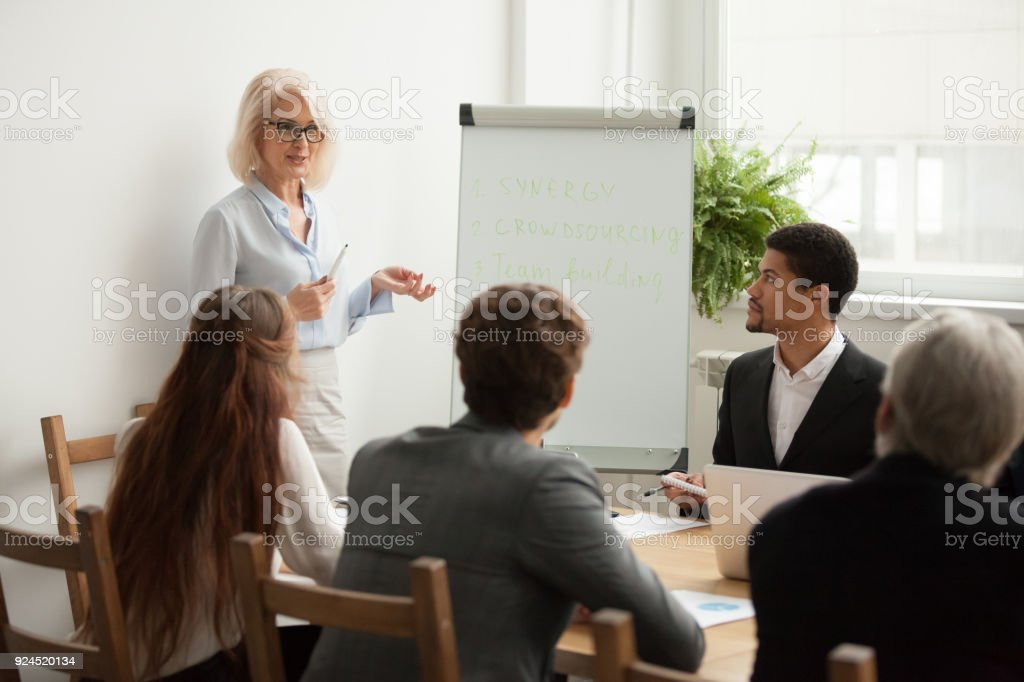 Aged attractive businesswoman giving presentation at corporate team meeting stock photo