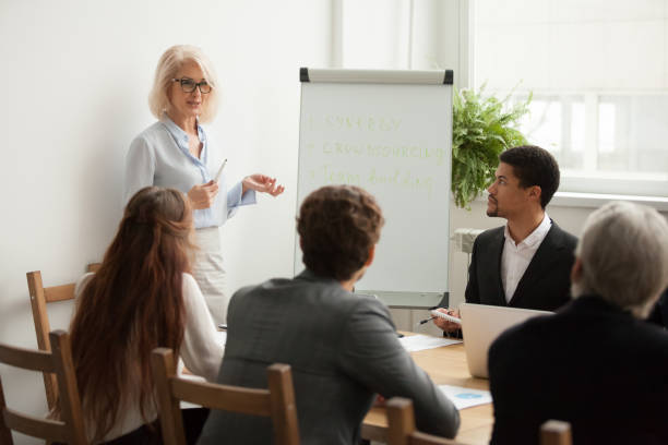 Aged attractive businesswoman giving presentation at corporate team meeting - foto stock