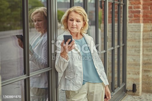 Elderly caucasian pretty business woman about 62 years old with mobile phone in her hand is reading message with serious face. She is wearing fashionable clothes being outdoors.