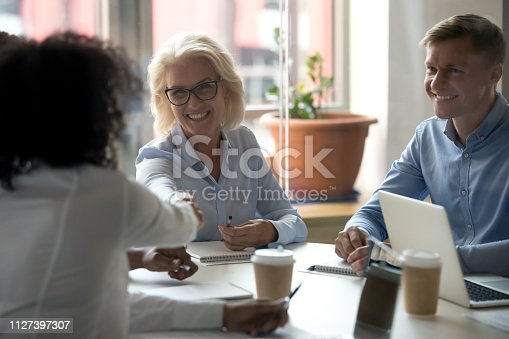 istock Aged businesswoman shaking hands with company client during business meeting 1127397307