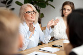 istock Aged businesswoman, teacher or business coach speaking to young people 924520276