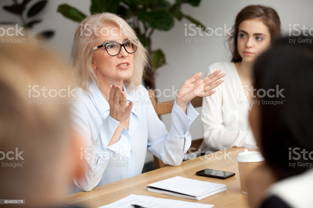 Aged businesswoman, teacher or business coach speaking to young people stock photo