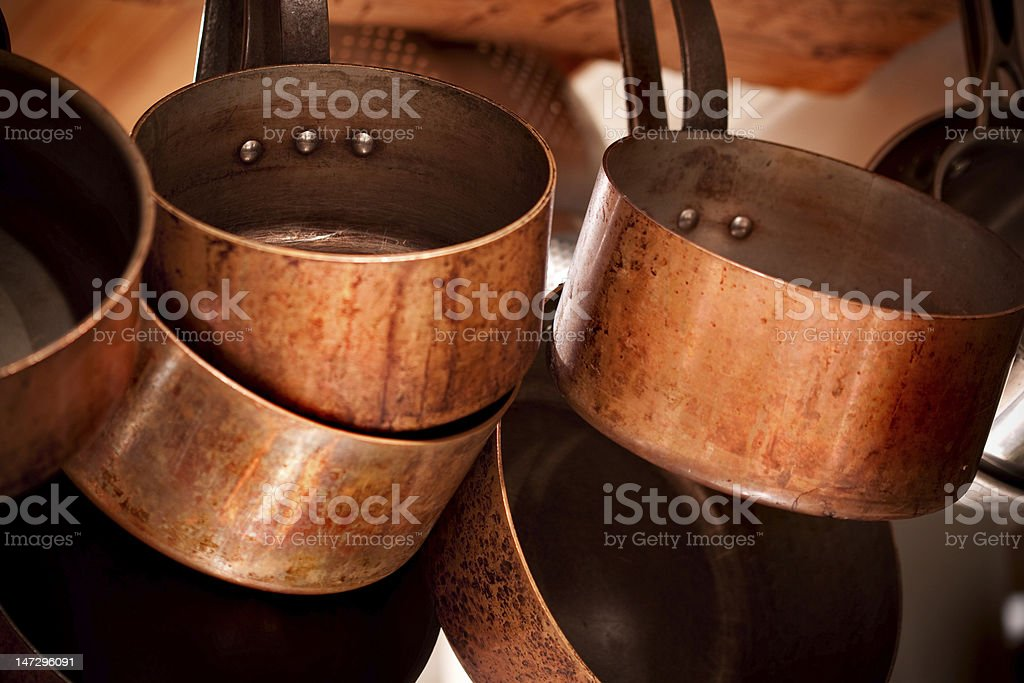 Aged copper pots and pans hanging on a rack stock photo