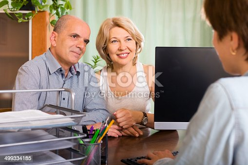 584597964 istock photo aged couple of pensioners talking with employee 499334185