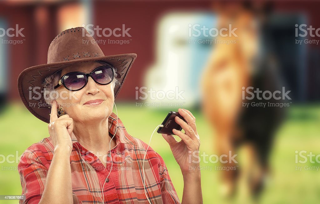 Aged cowgirl listening music with smart phone stock photo