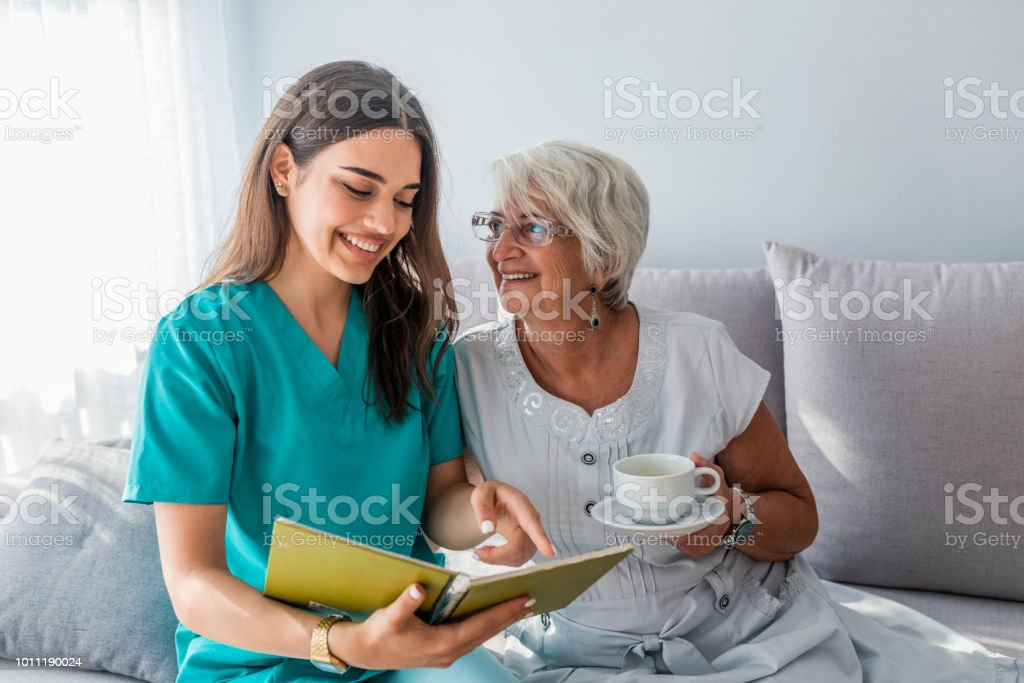 Happy patient is holding caregiver for a hand while spending time...
