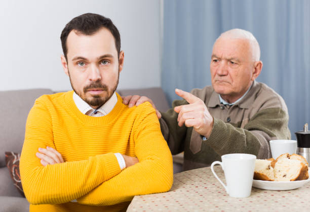 Aged father teaches his son stock photo