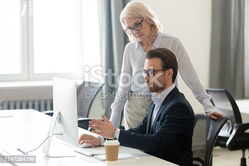 926404274 istock photo Aged female boss listens young manager asking about task 1147384799