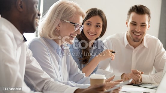 637940820 istock photo Aged female boss positive staff working together sitting at boardroom 1147384868