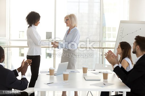 924520144 istock photo Aged female boss shaking hands with promoted worker 1125941847