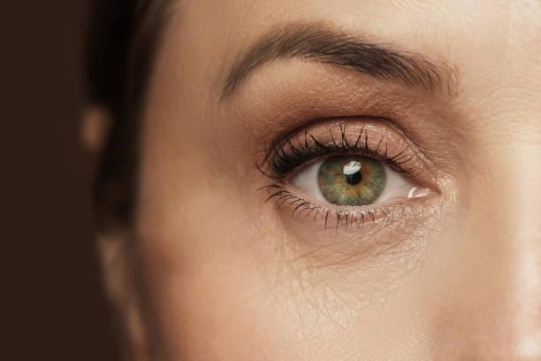 Aged female eye with wrinkled skin stock photo