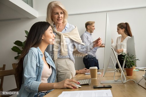 926404274 istock photo Aged female mentor helping asian girl intern explaining computer work 926404316