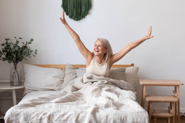 Aged female waking up in morning stretches seated in bed Refreshed elderly 50s female wakes up in morning stretches seated in bed in light bedroom at home, middle-aged woman feels happy and peppy after enough sleeping, greeting new day, good morning concept fresh start morning stock pictures, royalty-free photos & images