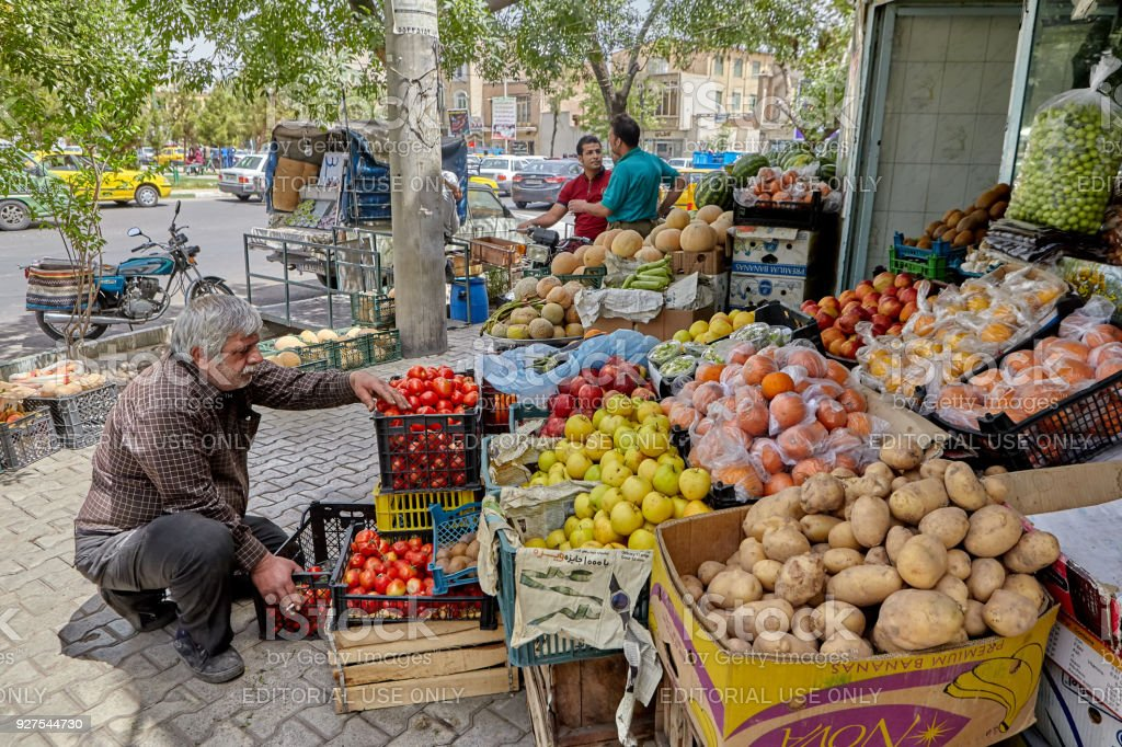 Aged fruiterer lays out their wares for sale, Kashan, Iran. stock photo