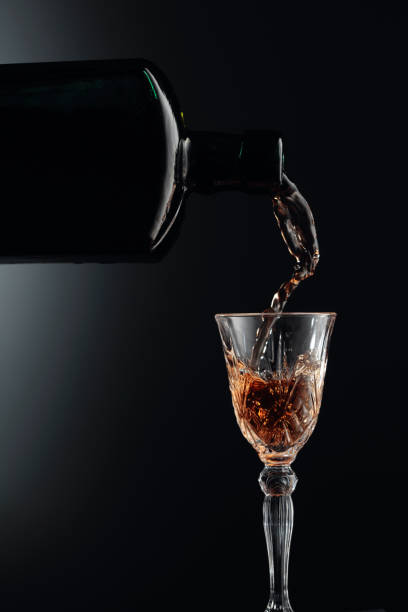 Aged golden fortified wine from the antique bottle being poured into a crystal glass. stock photo