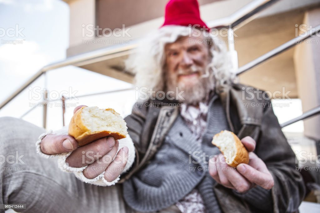 Aged homeless man sharing his bread zbiór zdjęć royalty-free