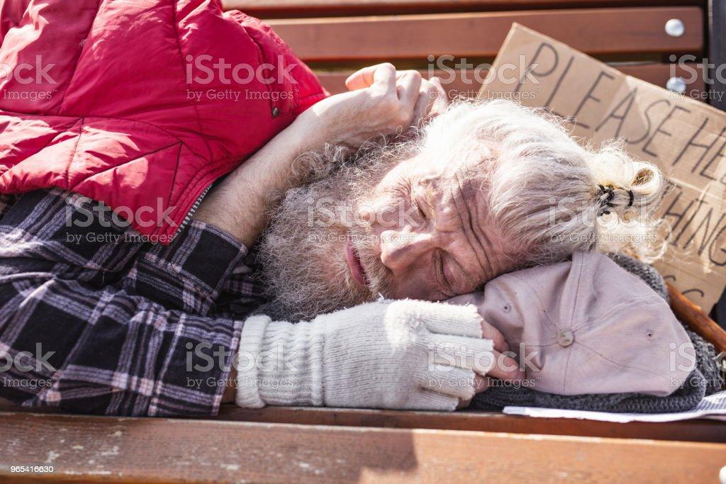 Aged homeless man sleeping on the bench zbiór zdjęć royalty-free