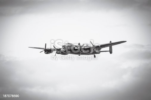 An aged image of an Avro Lancaster bomber in flight.  Black and white photo with vignette for ageing effect.  Made famous for the Dambuster raid on the Ruhr Valley by 617 Squadron of Air Marshal Sir Arthur Harris's RAF Bomber Command, commanded by Wing Commander Guy Gibson 1943.  Lancaster is flying diagonally towards the camera from right to left.  Background is clear with the aeroplane in the center of the image.