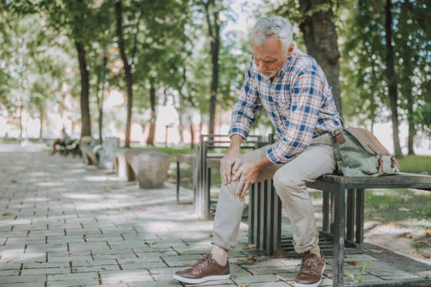 Aged man having sudden ache in his knee stock photo stock photo