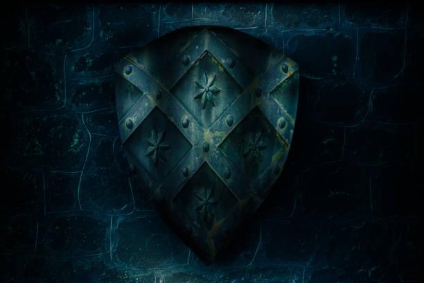 aged medieval shield over castle stone wall - средневековье стоковые фото и изображения