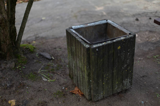 Aged outdoor wooden grey trash waste bin stock photo