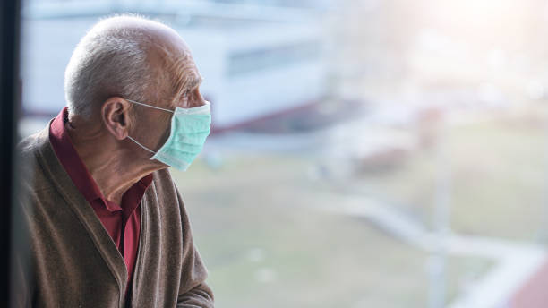 aged pensioner man with gray hair wearing medical facemask aged pensioner man with gray hair wearing medical facemask looking through window health care concept only senior men stock pictures, royalty-free photos & images