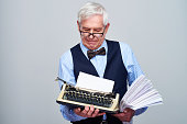 Senior elegant man holding retro typewriter and papers while contemplating on gray background