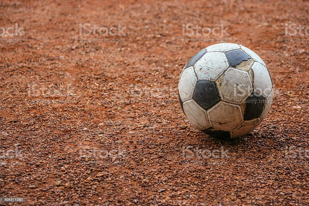 Aged soccer ball on ground stock photo