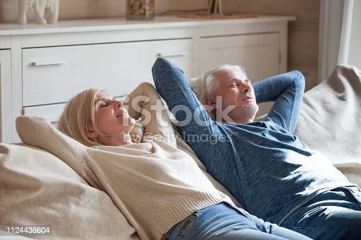 938682762istockphoto Aged spouses lying on couch putting hands behind head 1124436604