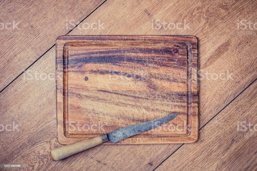 Envelhecido vintage placa de cozedura e faca no antigo fundo de tabela de madeira de carvalho. Foto filtrada estilo retro - foto de acervo