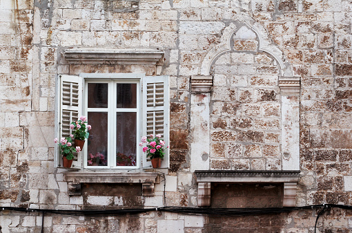 istock Aged windows and flower boxes of historical building from old town of Pula, Croatia / Detail of ancient venetian architecture with decorative elements / Material, texture, background and wallpaper. 941104126