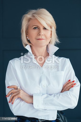 istock aged woman confidence elegance stylish arms folded 1141329984