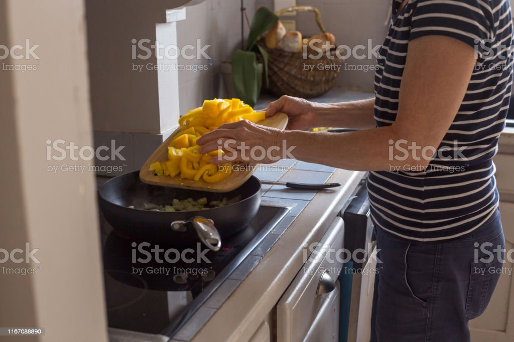 aged woman hands in process of cooking and cutting vegetables step by...